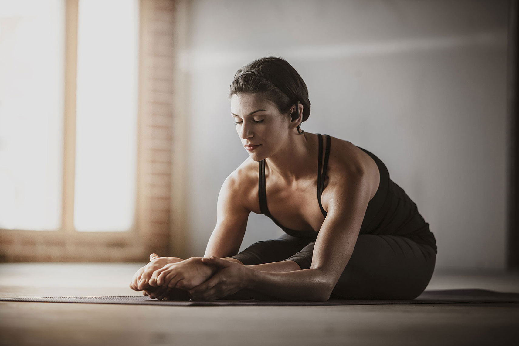 A women stretching on a yoga matt. | John Fedele Lifestyle Photography
