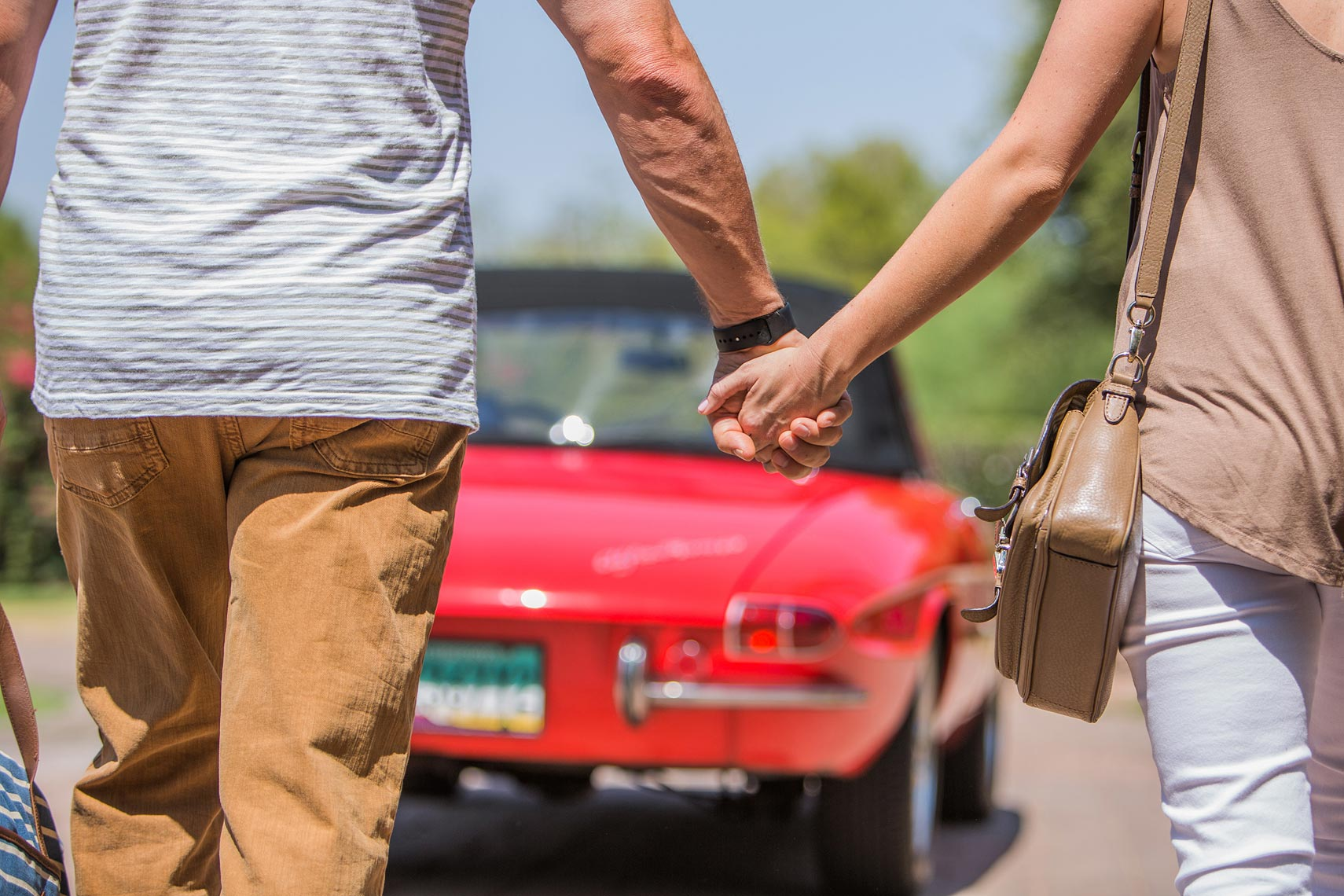 Coupe holding handing walking toward their car | OneAZ | John Fedele Lifestyle Photography