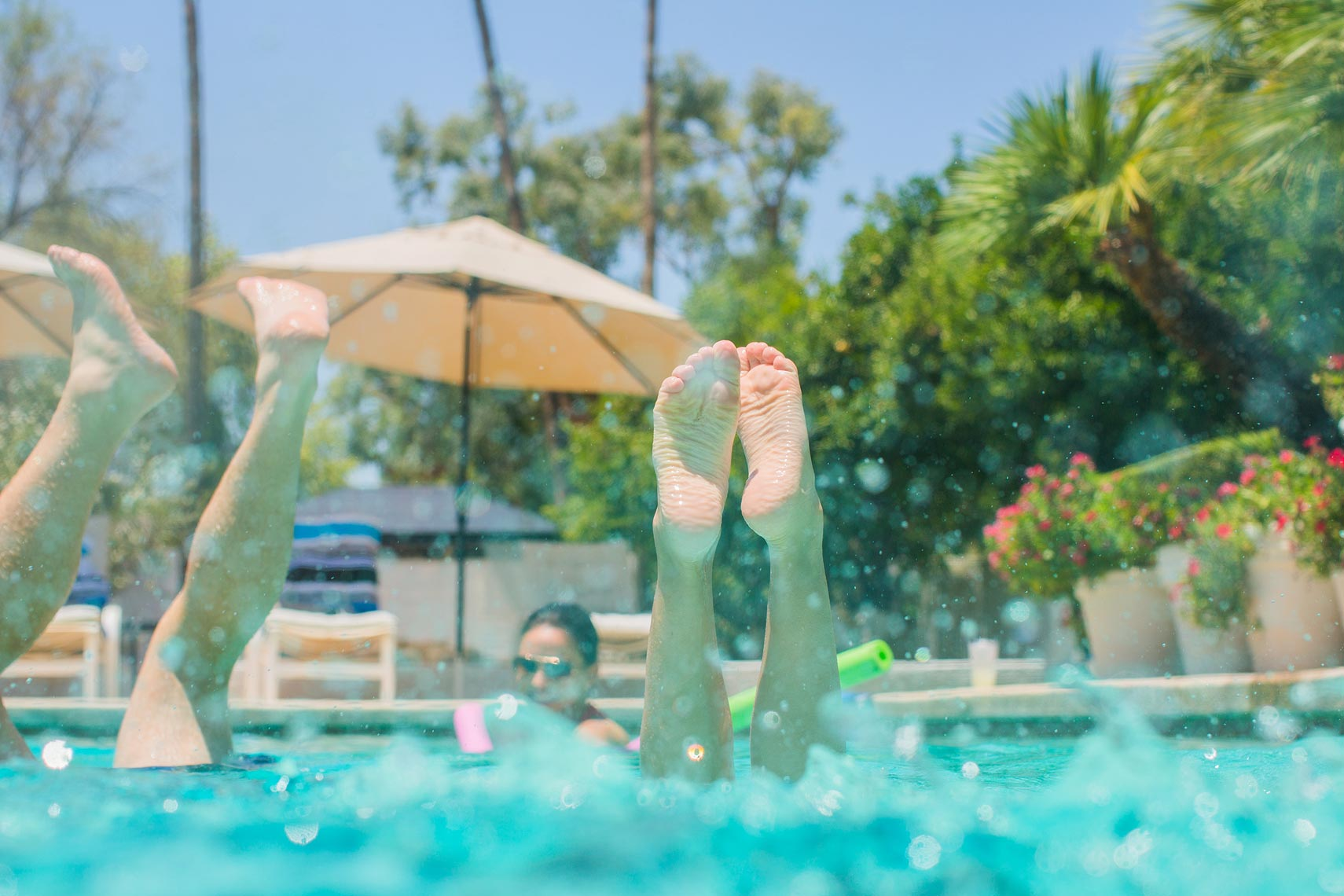 Kids swimming at a pool with their feet sticking out of the water | OneAZ | John Fedele Lifestyle Photography