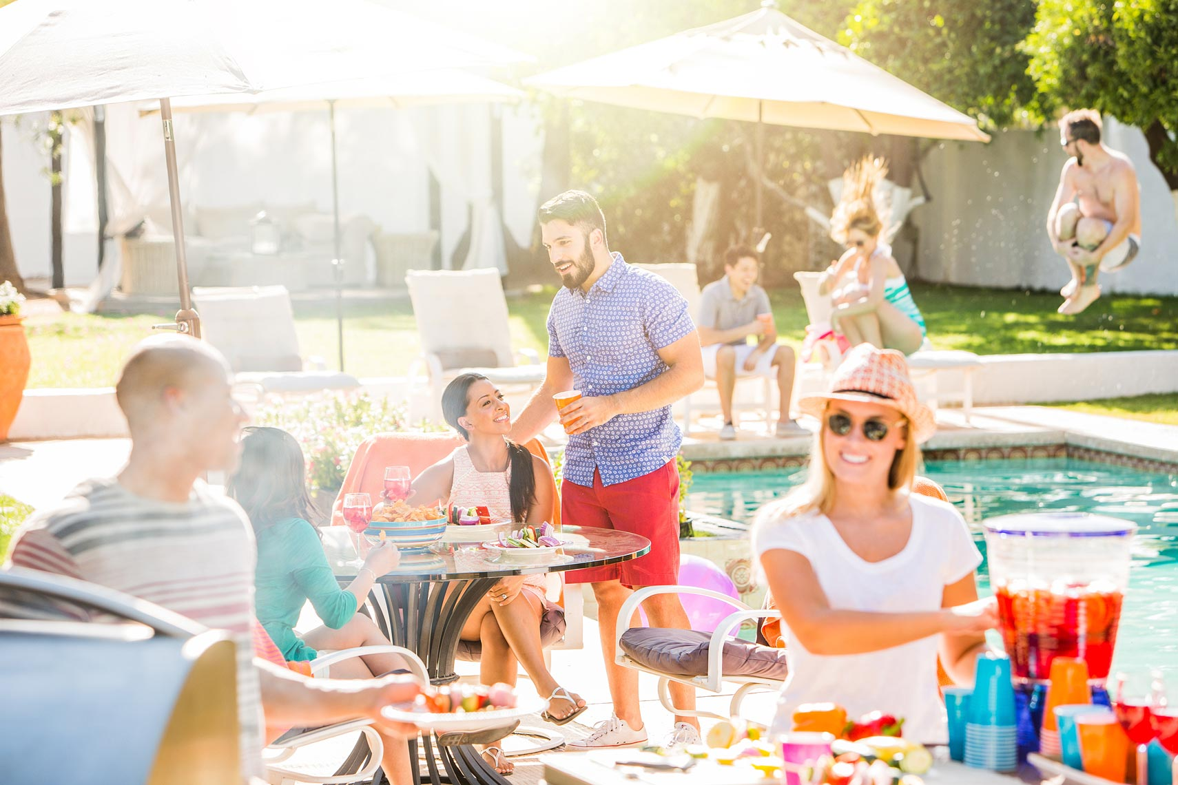 Friends laughing and eating at a backyard pool party | OneAZ | John Fedele Lifestyle Photography