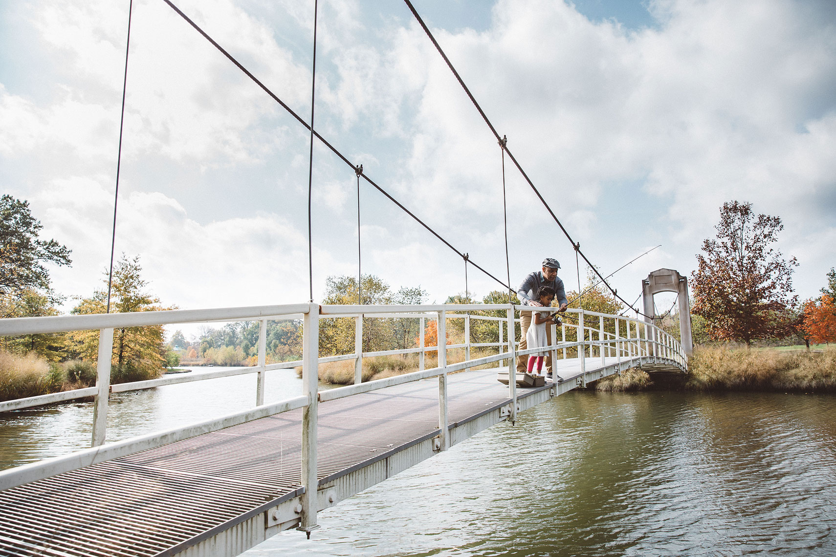 Grandfather and granddaughter fishing off a bridge |  Centene | John Fedele Lifestyle Photography