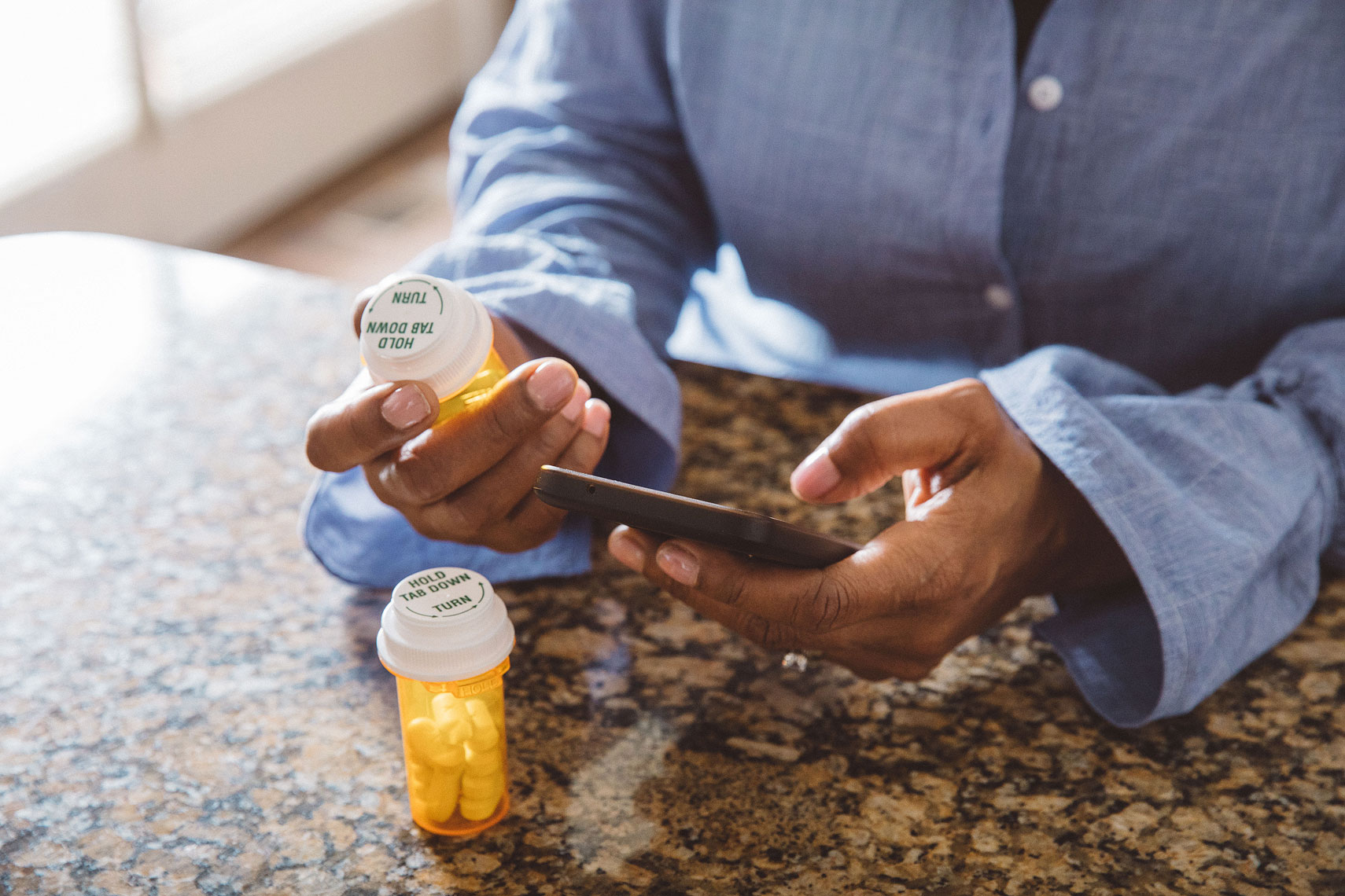 Woman holding a prescription bottle and a cell phone |  Centene | John Fedele Lifestyle Photography