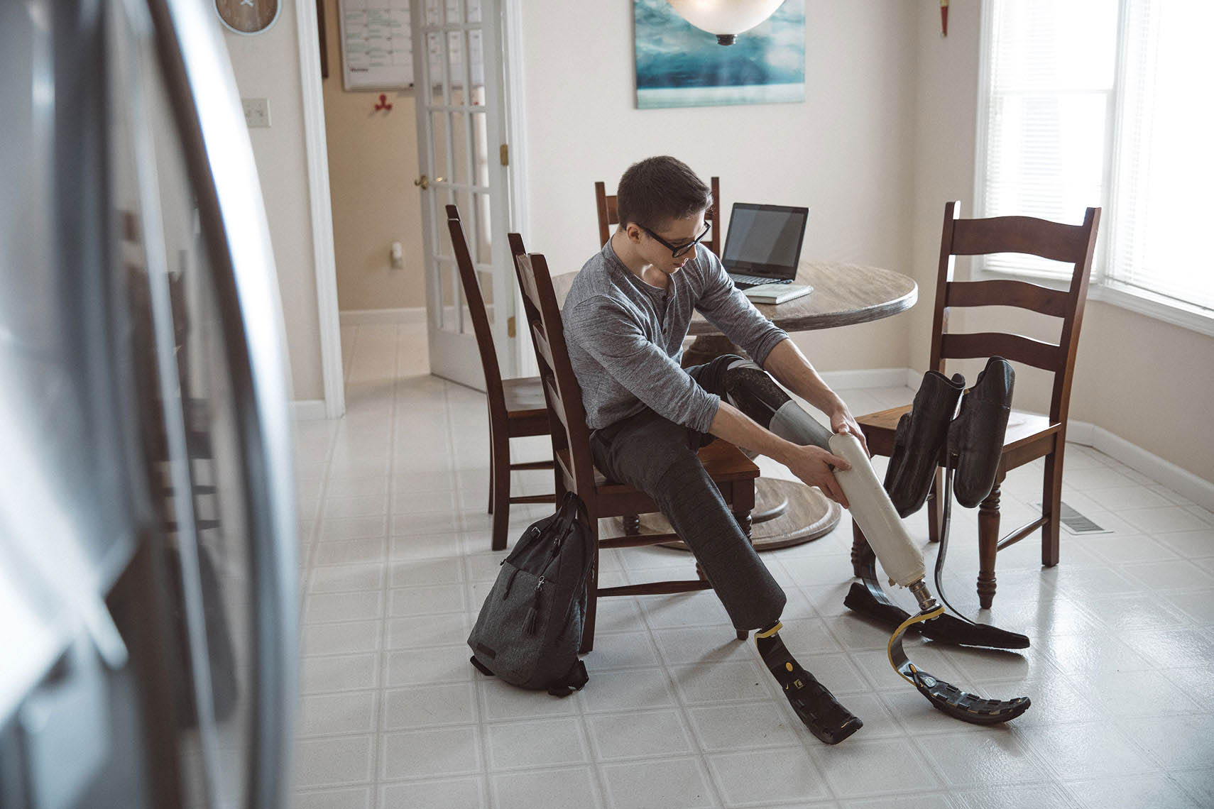 Man attaching his prosthetic legs at the kitchen table |  Centene | John Fedele Lifestyle Photography
