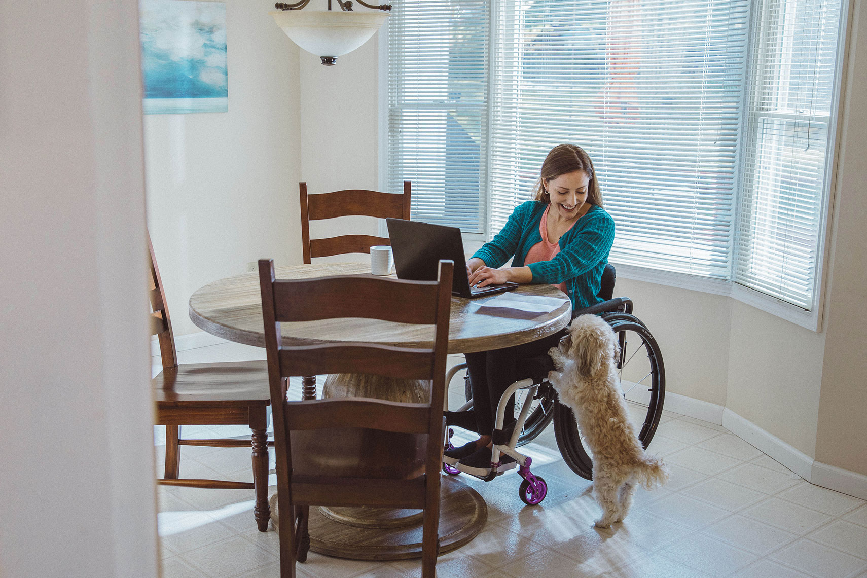 Women in wheelchair with dog at the kitchen table |  Centene | John Fedele Lifestyle Photography