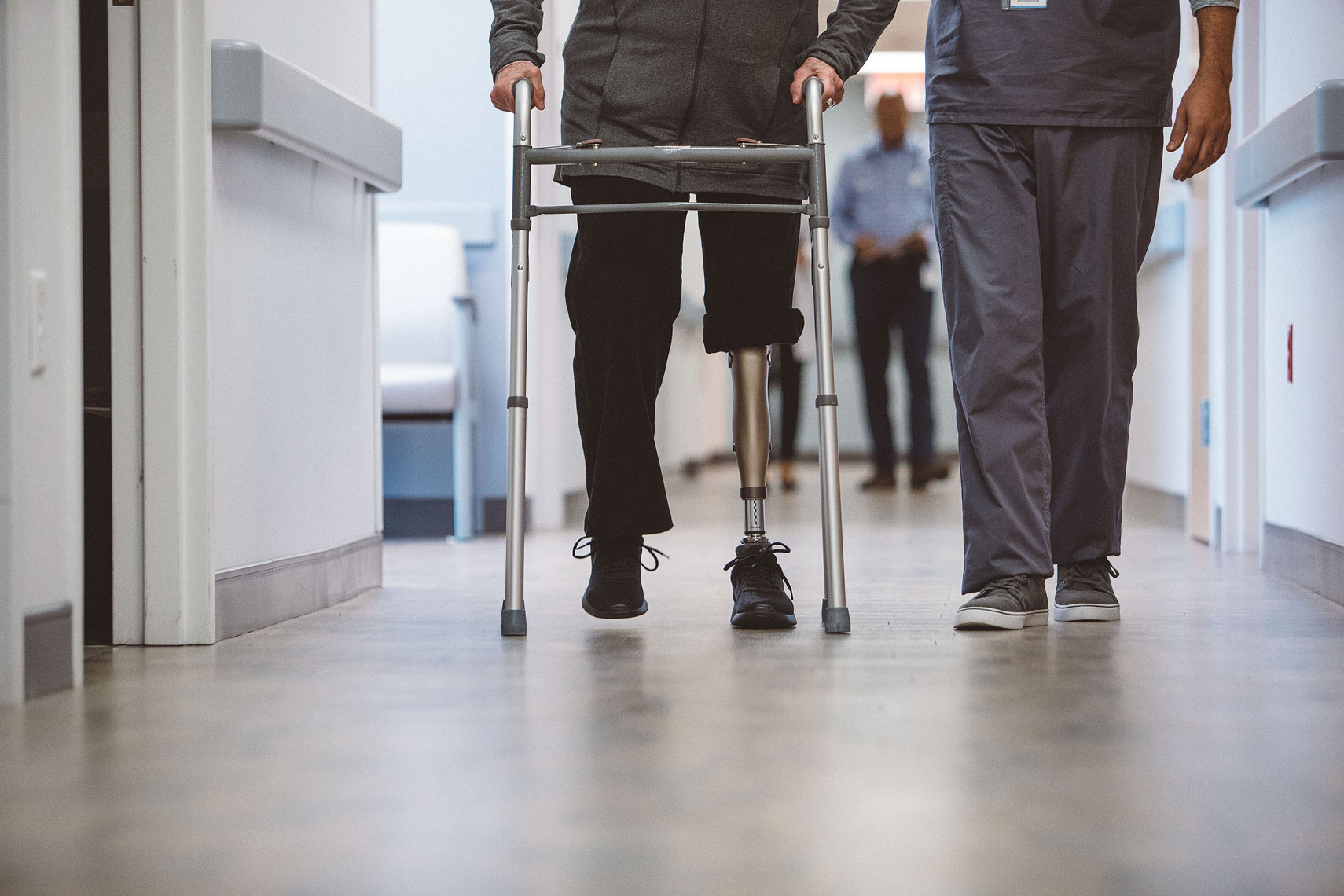 Patient with a prosthetic leg walking with a walker and a nurse |  Centene | John Fedele Lifestyle Photography