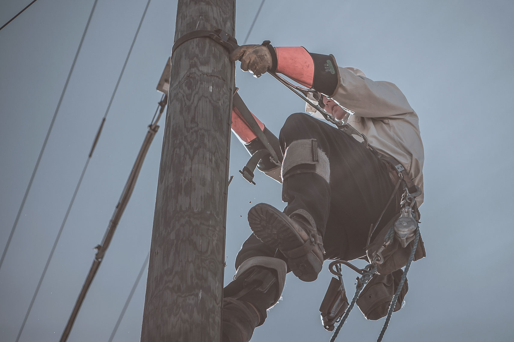 Worker climbing up a phone pole | Touchstone Energy | John Fedele Industrial Photography