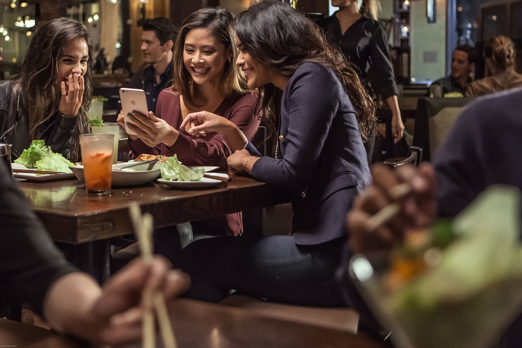 Women enjoying Chinese food while looking at a phone | P. F. Chang
