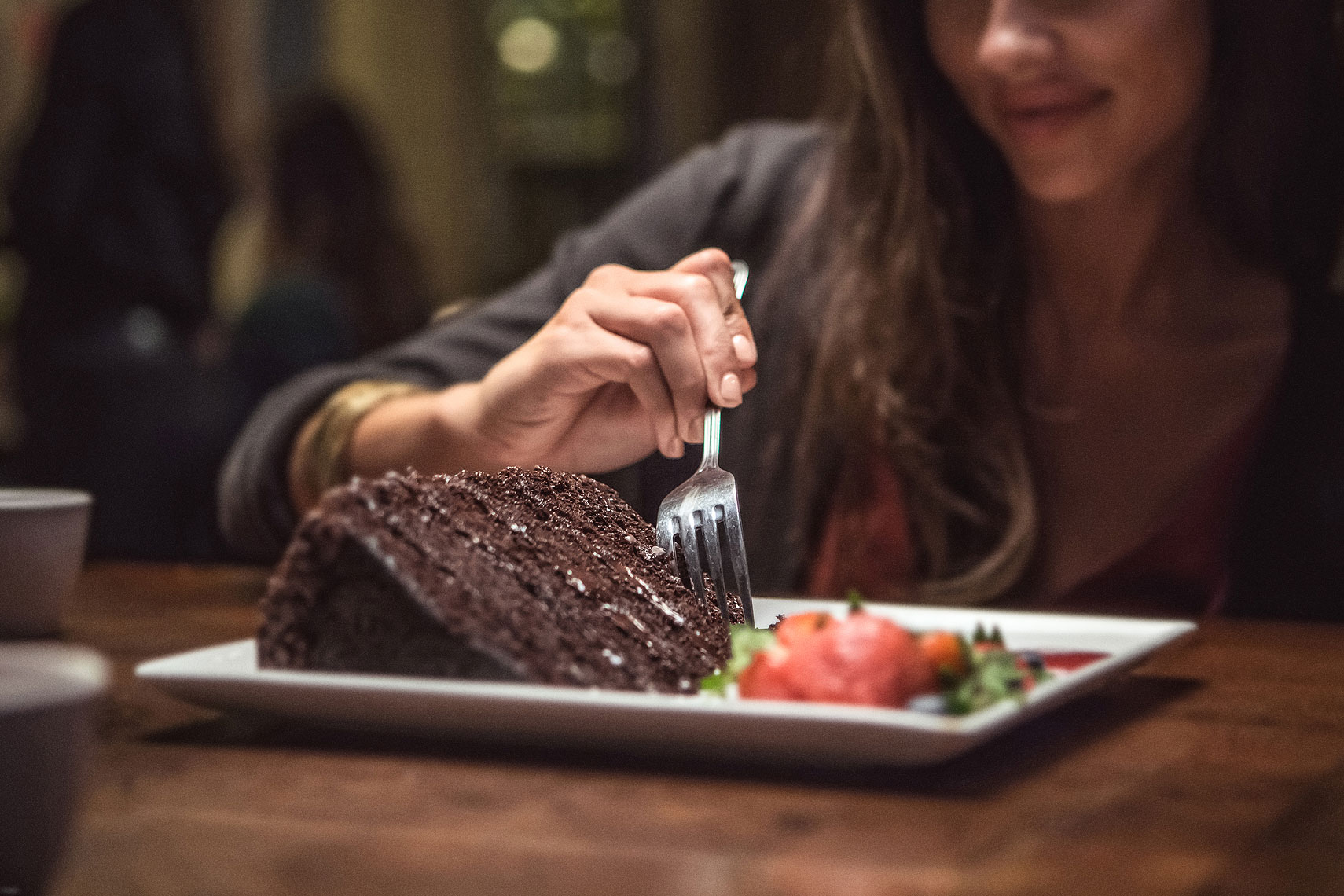 Women taking a bite out of a large piece of chocolate cake | P. F. Chang