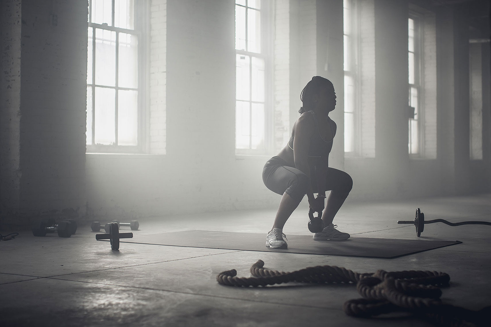 Women working out in an industrial gym with a kettle bell. | John Fedele Lifestyle Photography