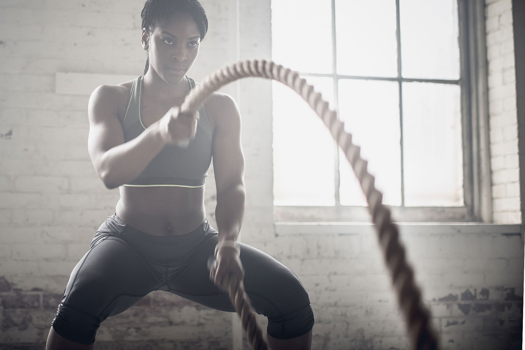 Woman working out with battle ropes. | John Fedele Lifestyle Photography