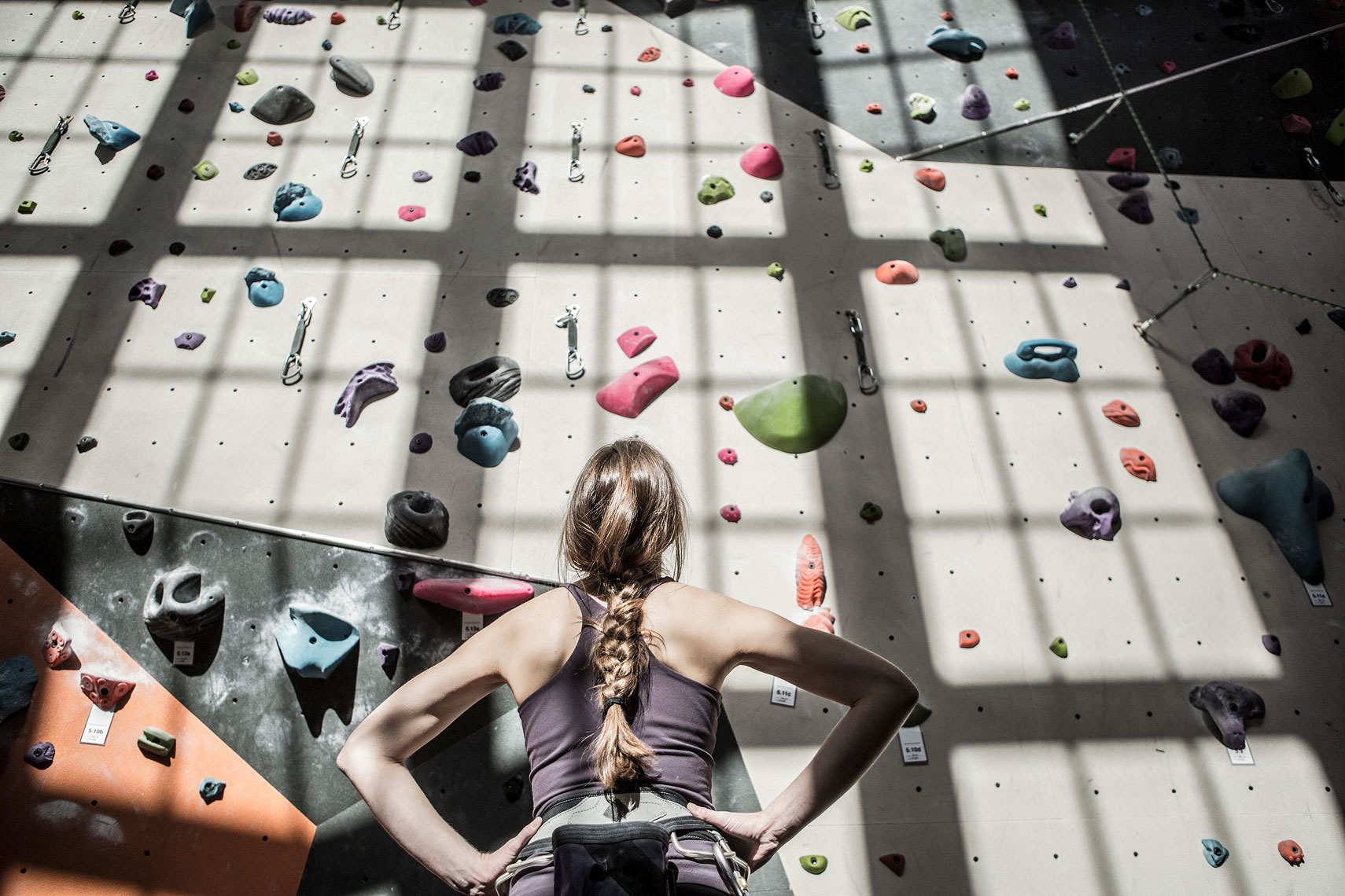 Woman facing up to a climbing wall. | John Fedele Lifestyle Photography