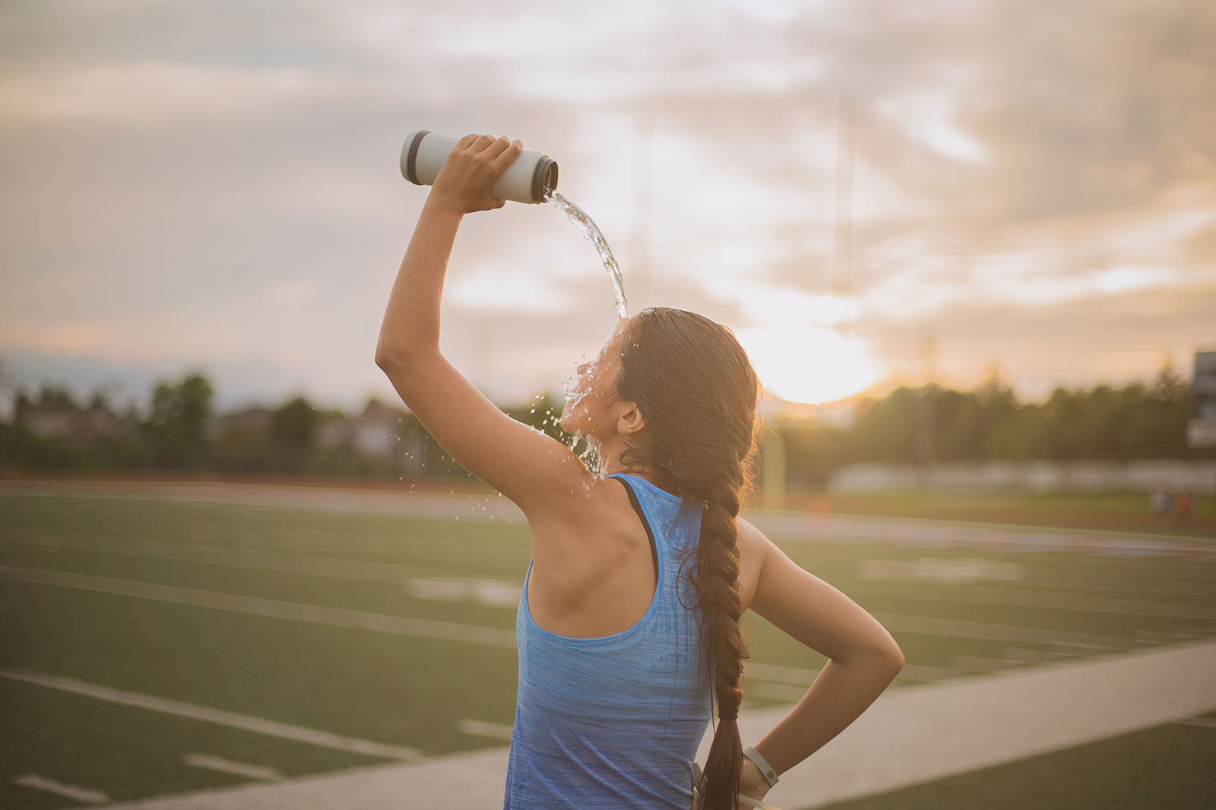 Woman pouring water over her head to cool off. | John Fedele Lifestyle Photography