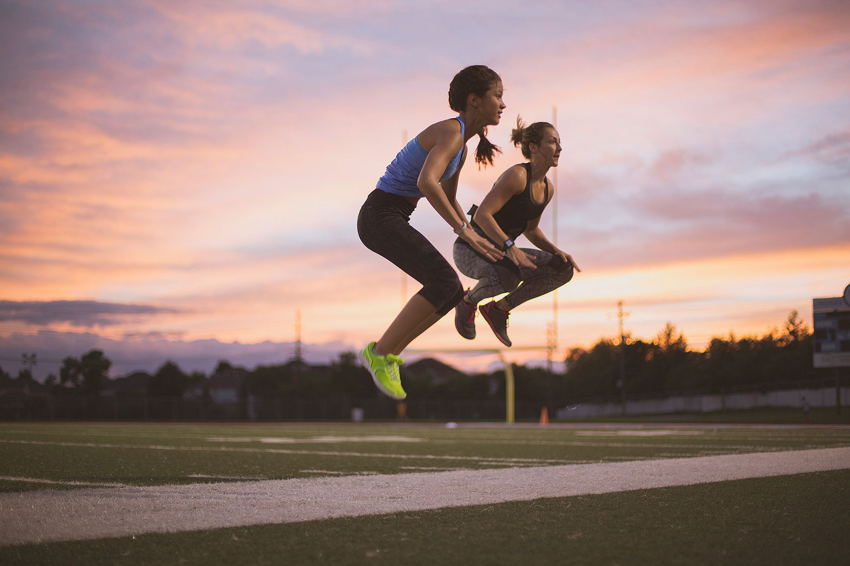 Two women doing jump squats at sunset on a track. | John Fedele Lifestyle Photography