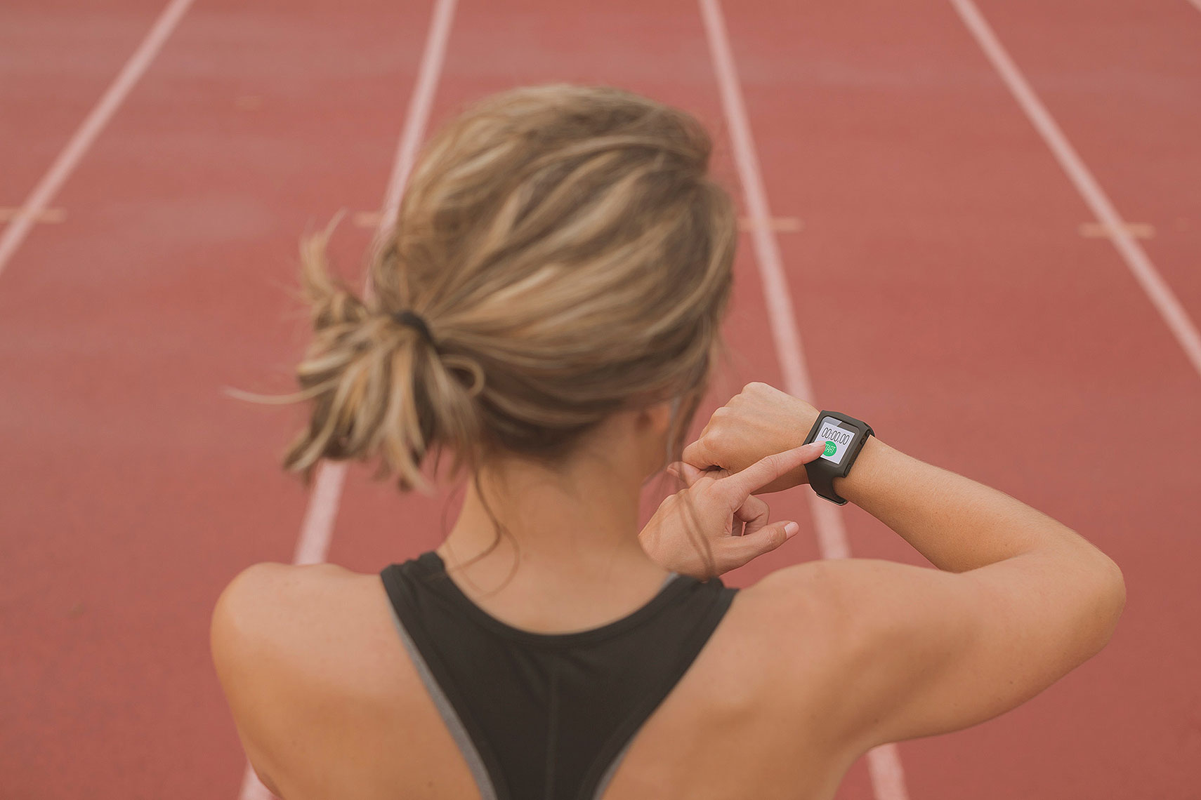 Woman setting her fitness tracker on a track. | John Fedele Lifestyle Photography