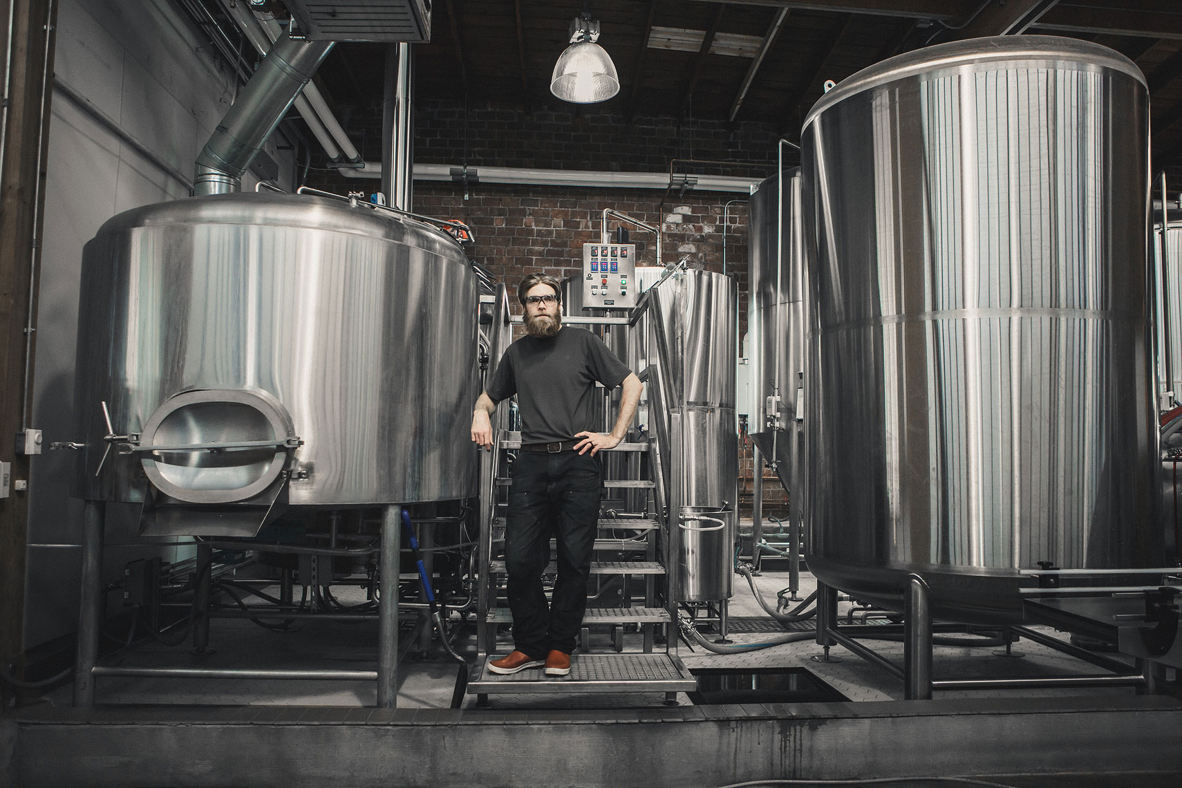 Man standing in a brewery in front of fermentation vats | Side Project Brewery | John Fedele Photography