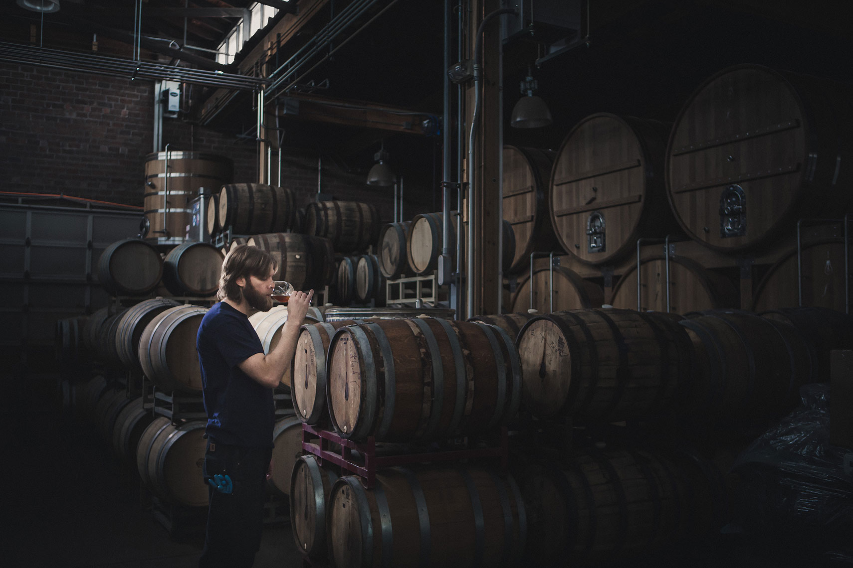 Man tasting a beer out of aging whiskey barrels in a warehouse | Side Project Brewery | John Fedele Photography