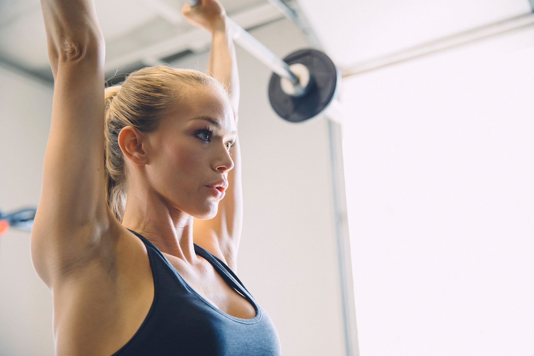 Close up of a woman lifting weights. | John Fedele Lifestyle Photography