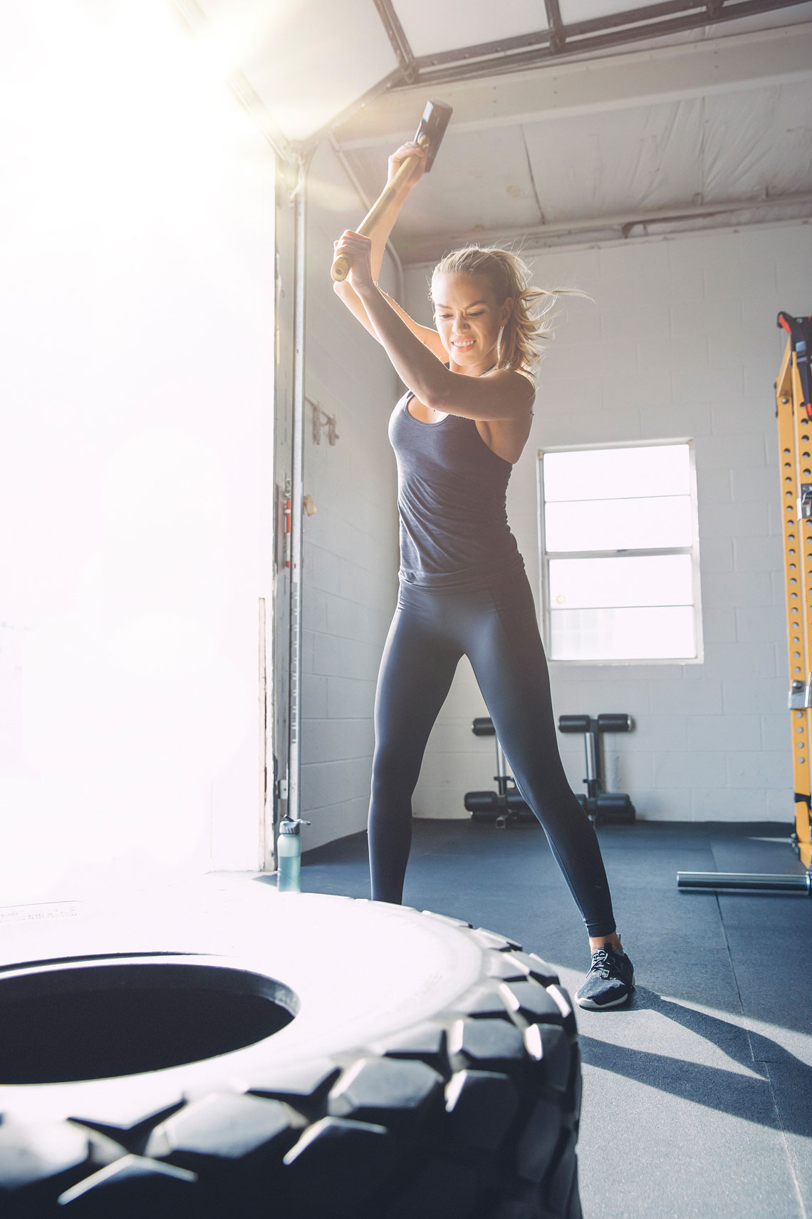 Women swinging to hit a tire with a sledgehammer in a gym.  | John Fedele Lifestyle Photography