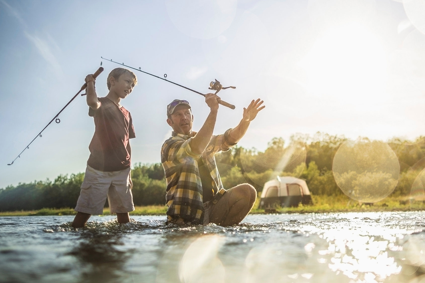 Father teaching his son to fish in a river.  | John Fedele Lifestyle Photography