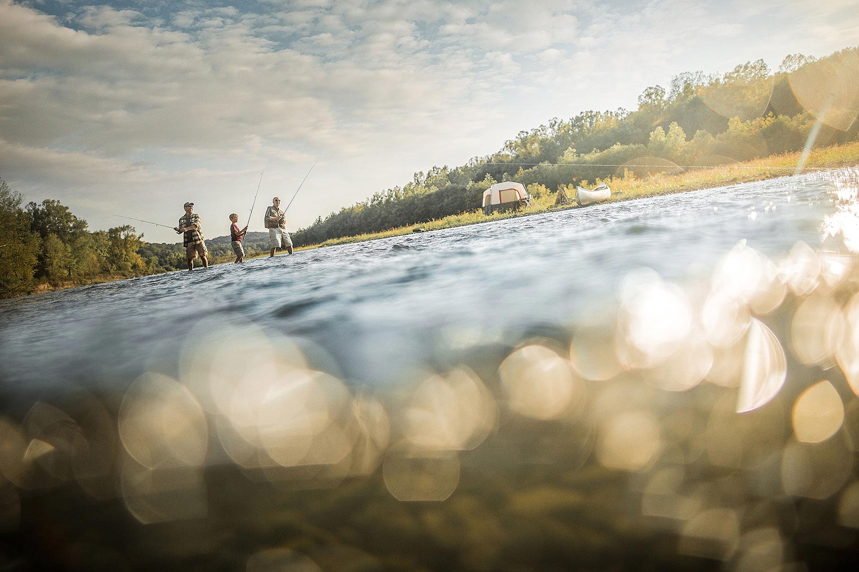 Family fishing in a river with their campsite in the background. | John Fedele Lifestyle Photography
